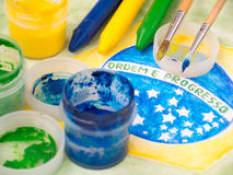 Paints,brushes and crayons on the brazil flag watercolor paintin Royalty Free Stock Photography