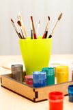 Paints and brushes in a cup ready for painting Stock Image