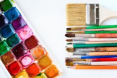 Paints, brushes of different sizes and pencils  for drawing  on white texture background. Art and education object stock images