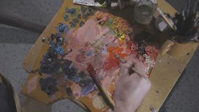 Paints and brushes on the easel.  stock video