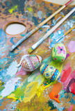 Paints, brushes and Easter eggs. Stock Photo