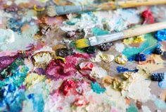 Paints and brushes. Brushes lie among multi-colored paints Stock Images