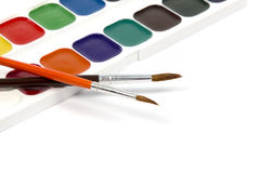Paints and brushes. New watercolor box with two brushes isolated on white background Royalty Free Stock Images