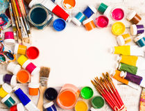 Paints, brushes and palette on the white wood background. Stock Images
