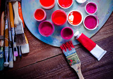 Paints, brushes and palette on the wood background. The workplace of the artist. Banner for school stock photos