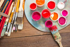 Paints, brushes and palette on the wood background. Royalty Free Stock Photography