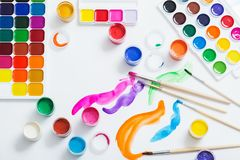 Paints and brushes on paper. The paints and brushes on paper royalty free stock images
