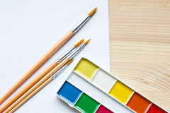 Paints, brushes and paper. On the table Stock Photos