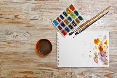 Paints, brushes and sketch pad. Tools of artist. Watercolor paint, brushes and sketch pad on a wooden table. Watercolor spots on the paper. Painter Tools group stock images