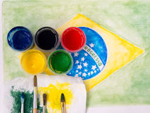 Paints,brushes and and stained fabric on the brazil flag waterco Royalty Free Stock Photography