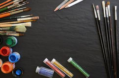 Paints and brushes on a table Stock Photography