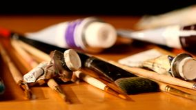 Paints and brushes, tubes of paint on wooden table stock footage