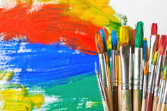 Paints and brushes. Vintage artists brushes and paint tubes on an abstract artistic background Royalty Free Stock Photo