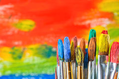 Paints and brushes. Vintage artists brushes and paint tubes on an abstract artistic background Stock Photography