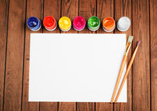 Paints and brushes on a white blank sheet of paper on wooden bac. Kground Stock Image
