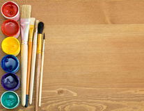 Paints and brushes on wooden table. Colorful paints and brushes on wooden table stock photography
