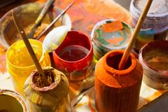 Paints and brushes in the workplace in the artist studio royalty free stock photography