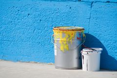 Paints cans near a blue wall. Paint cans in front of a blue wall where are making a drawing stock image