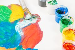 Paints of Different colors and paint brush on white table. The brush and paints of various colors and red and green and yellow and blue are spilled on white Stock Image