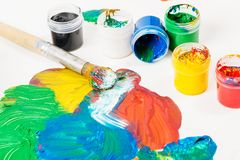 Paints of Different colors and paint brush on white table. The brush and paints of various colors and red and green and yellow and blue are spilled on white Royalty Free Stock Image