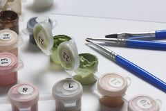 Paints for drawing by numbers. Several containers with paint are open. There are tassels, a sheet of paper nearby. Paints for drawing by numbers. Several Royalty Free Stock Photography