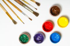 Paints in jars and a brush on a white sheet of paper Royalty Free Stock Photography