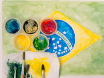 Paints lids,brushes and and stained fabric on the brazil flag wa Royalty Free Stock Image