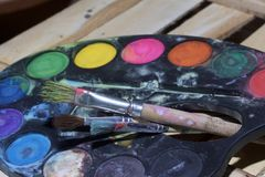 Paints and paint brushes lie on a wooden plank of boards. Paints and paint brushes lie on a wooden plank of boards Royalty Free Stock Photography