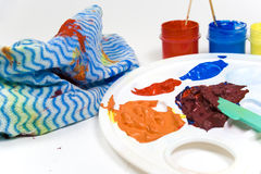 Paints on plastic palette. Details of colored paint on a plastic artist palette with a cleaning towel or rag nearby royalty free stock image