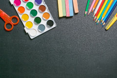Paints, scissors, pencils and chalks on black chalkboard 1 Stock Images