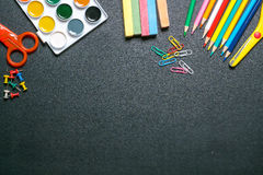 Paints, scissors, pencils and chalks on black chalkboard 2 Royalty Free Stock Images