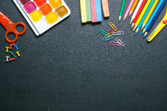 Paints, scissors, pencils and chalks on black chalkboard 3 Royalty Free Stock Photography