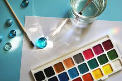 Paints and sheet of paper on blue background. Workplace of an watercolor artist-painter. Blue background, new beautiful paints and brashes. School concept royalty free stock photo