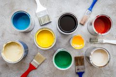 Paints in tin banks and brushes on grey stone background top view Royalty Free Stock Photos