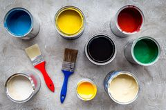 Paints in tin banks and brushes on grey stone background top view Royalty Free Stock Photo