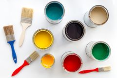Paints in tin banks and brushes on white background top view Stock Photos