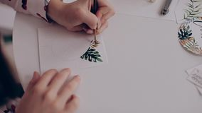 She paints in watercolor flowers, hand closeup stock video footage