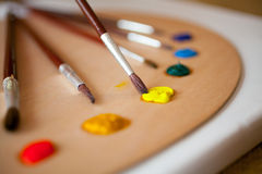 Paints on wooden pallet. Focus on paintbrush dipped in yellow pa. Colorful acrylic paints on wooden pallet. Focus on paintbrush dipped in yellow paint stock photo