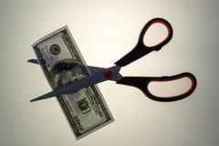 Paio di forbici che taglia la banconota in dollari di U.S.A. 100 Immagini Stock