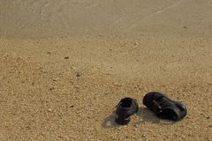 Brown sandals on a deserted beach royalty free stock photography