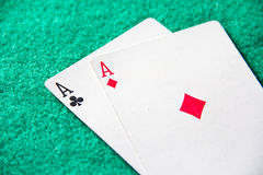 Pair of aces. Diamonds and clubs, on green baize background Royalty Free Stock Photos