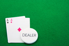 Pair of Aces for the Dealer on Green. A Pair of Aces with a Dealer button on Green felt Royalty Free Stock Photography