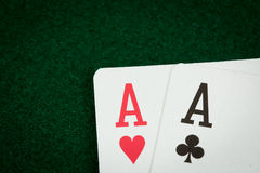 A pair of aces on a green poke table Royalty Free Stock Photo