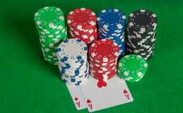 Pair aces and poker chips stack on green table Royalty Free Stock Images