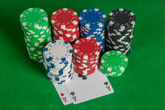 Pair aces and poker chips stack on green table Stock Photo