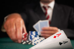 Pair of aces and poker player. Gambling casino chips on green felt background selective focus stock images