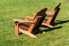Pair of Adirondack Chairs in a Lawn. A pair of Adirondack chairs in a lawn, facing left Royalty Free Stock Image