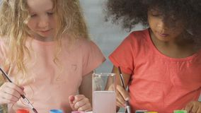 Pair of adorable kids drawing paintings for charity purposes, philanthropy. Stock footage stock footage