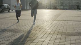 Pair of adult friends jogging in metropolitan area, slowly approaching camera. Stock footage stock video