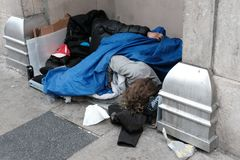 Homeless persons seen asleep during winter in a major city. stock photography